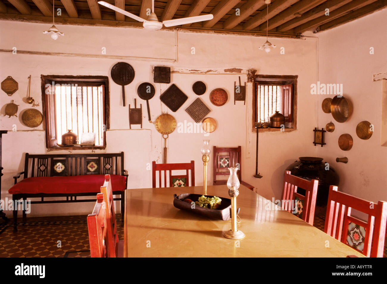 Wood beamed ceiling and kitchen utensils on wall in dining area in restored traditional Pol house Ahmedabad Gujarat - Stock Image