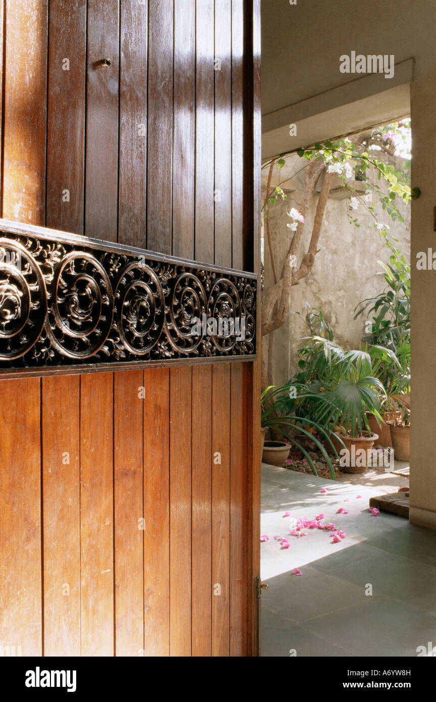 A modern front door decorated with a 400 year old piece of wood carving in 1970s concrete structured home Ahmedabad - Stock Image