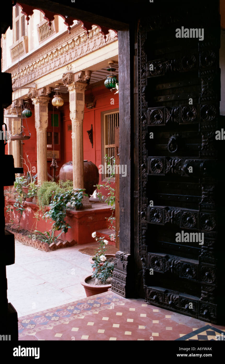 Traditional wood door and 19th century floor tiles in restored traditional Pol house Ahmedabad Gujarat state India - Stock Image