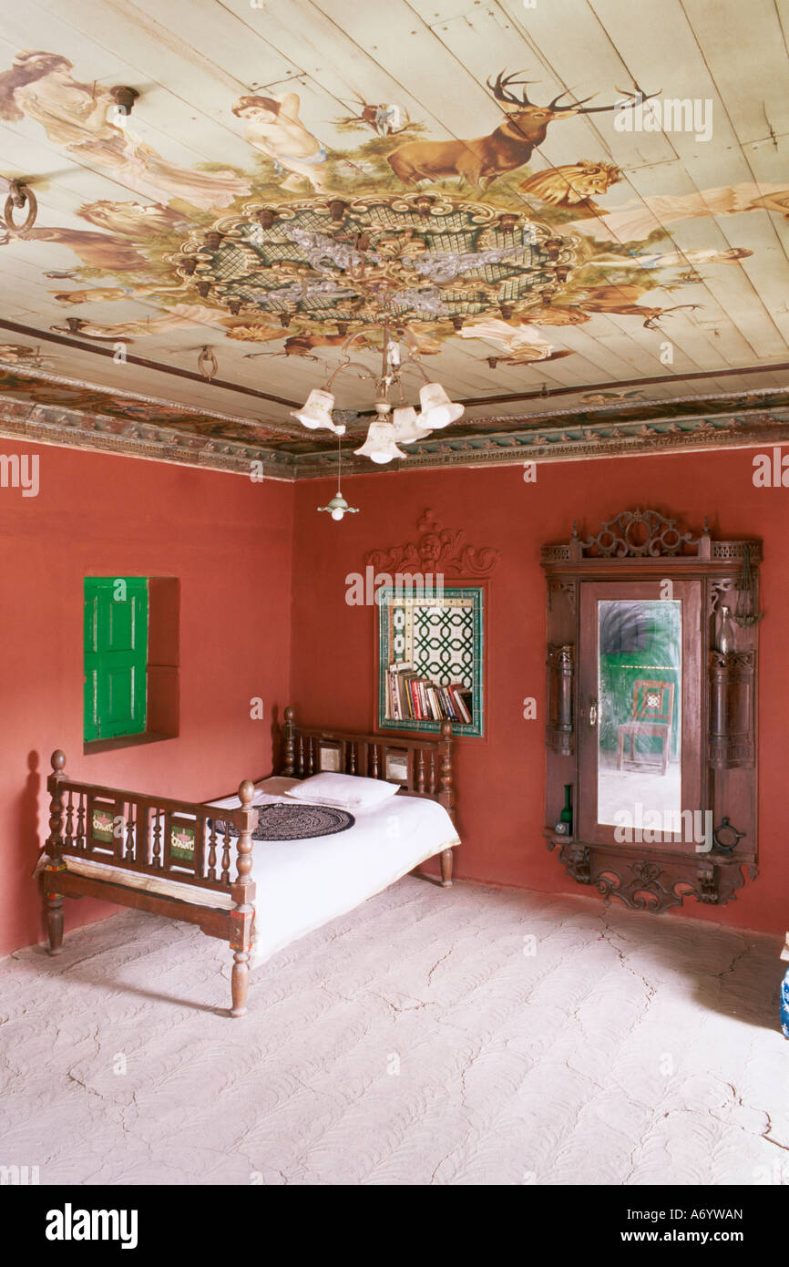 Traditional mud floor contrasting with the magnificently painted ceiling in restored traditional Pol house Ahmedabad - Stock Image