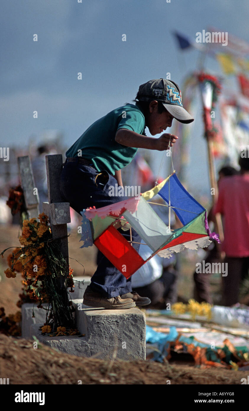 Boy with colourful paper kite standing on a tombstone 1 November celebrations at Santiago Sacatepequez GUATEMALA - Stock Image