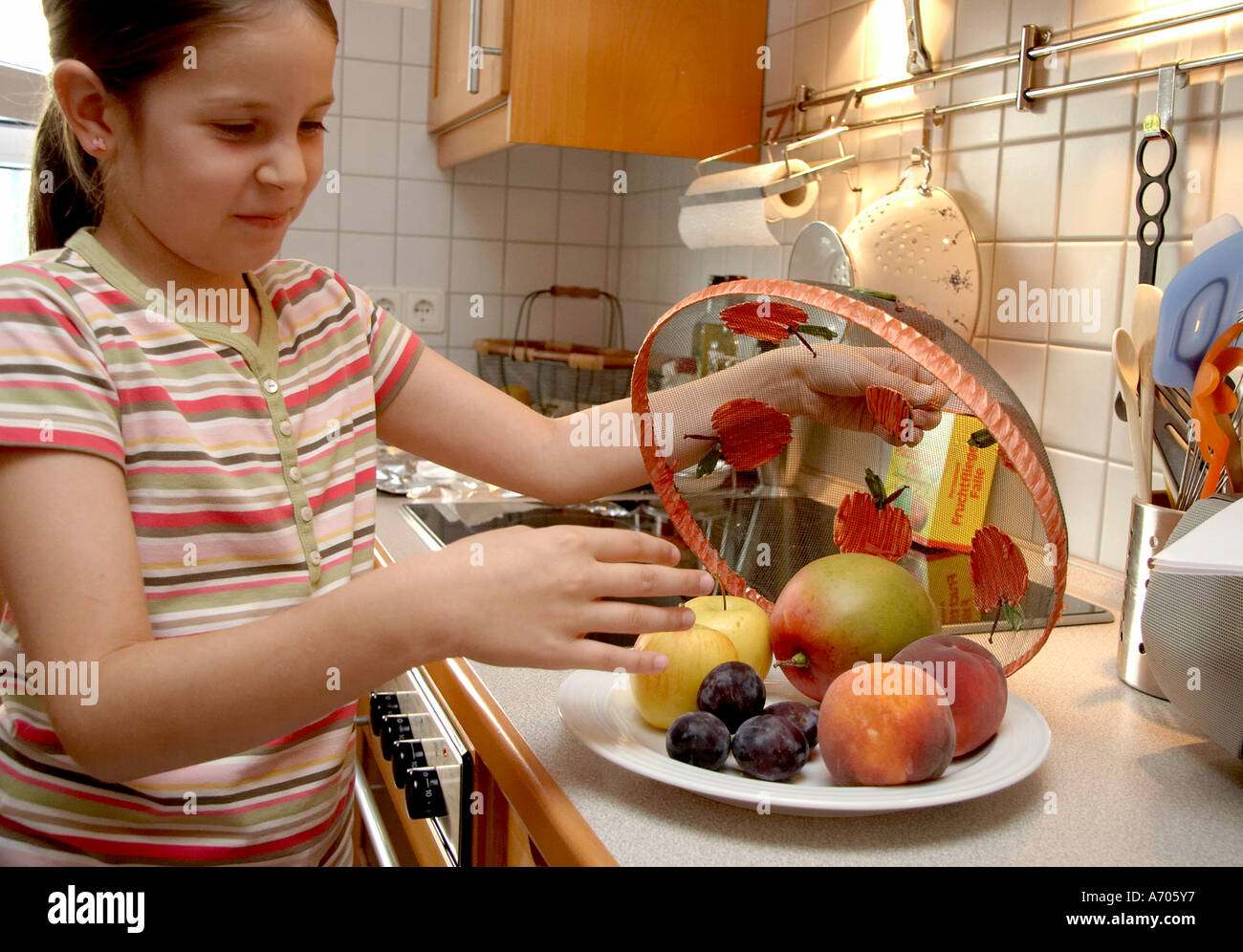 Fruit plate, Leonie looks at the fruit, she does not like it - Stock Image