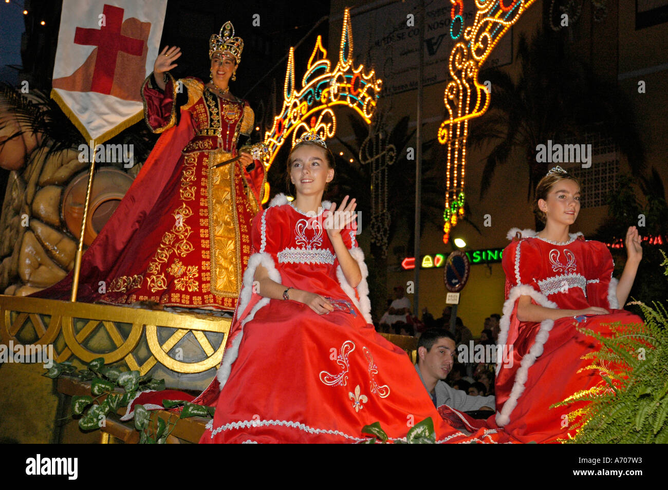 Three red dressed princesses on a car, Fiesta, moros y cristianos, Calpe, Costa Blanca, Spain - Stock Image