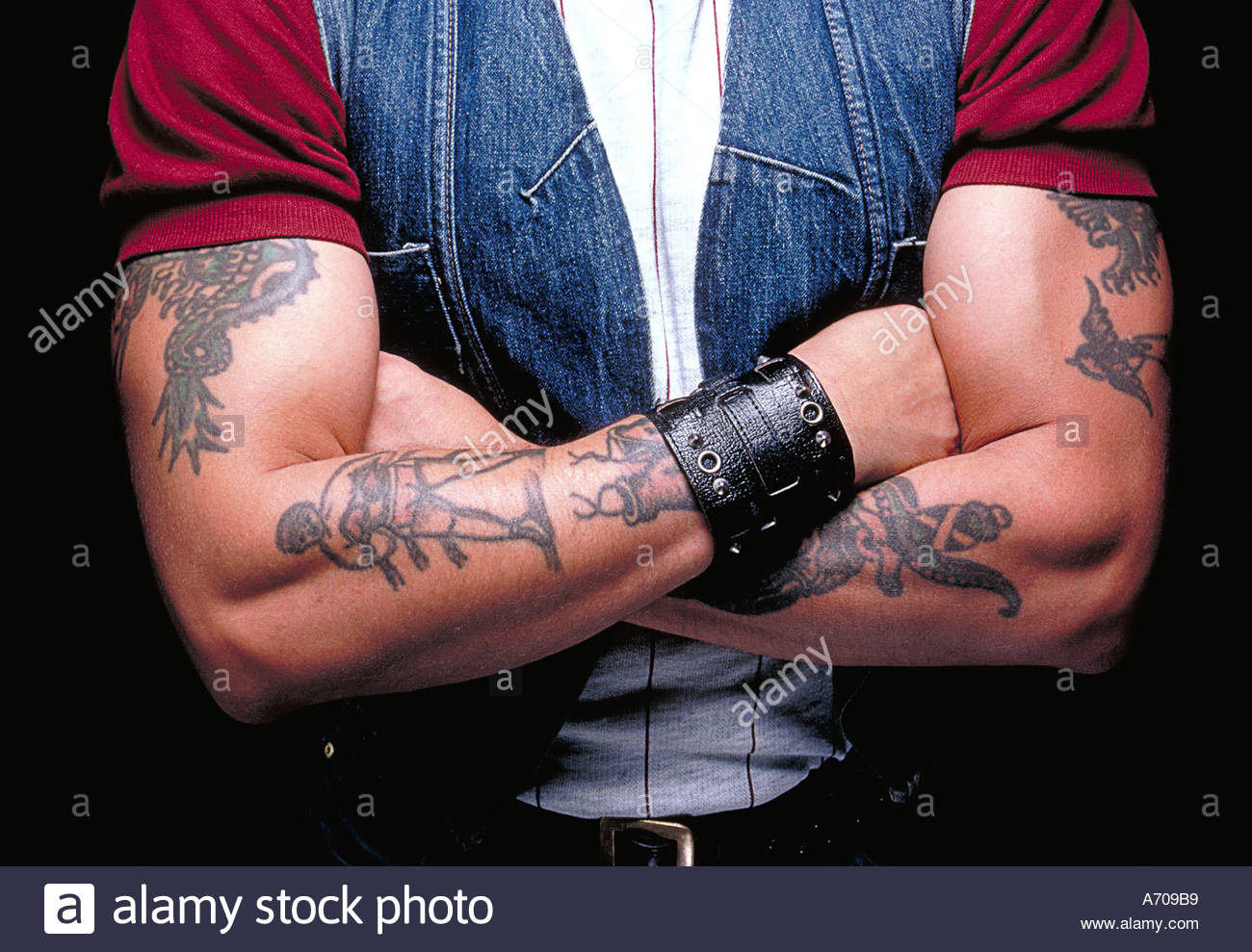 Man with tattoos on his folded arms - Stock Image