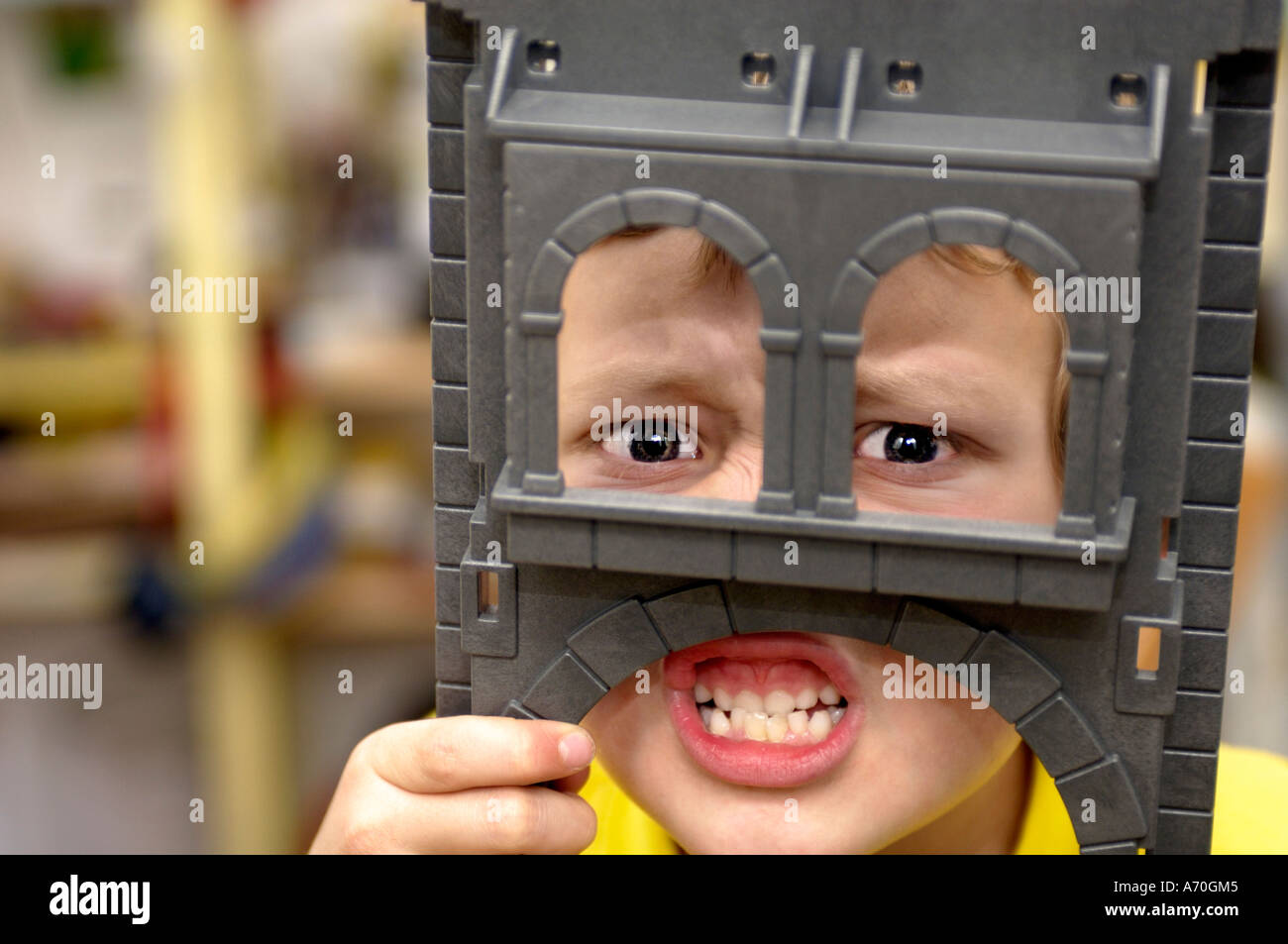 Young boy grimacing behind his toy knight's castle - Stock Image