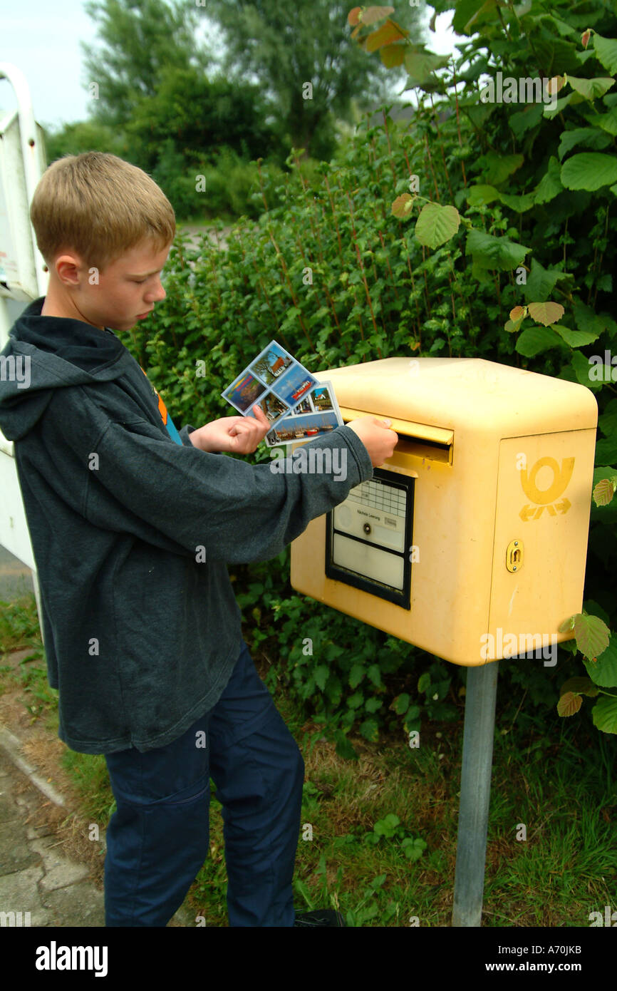 Teenager at the mail box sends picture postcards Stock Photo