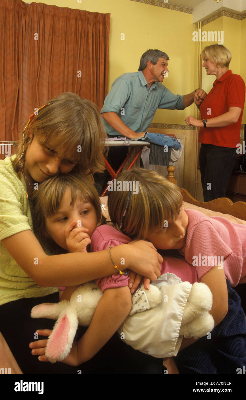 3 children cuddling each other while the parents argue - Stock Image