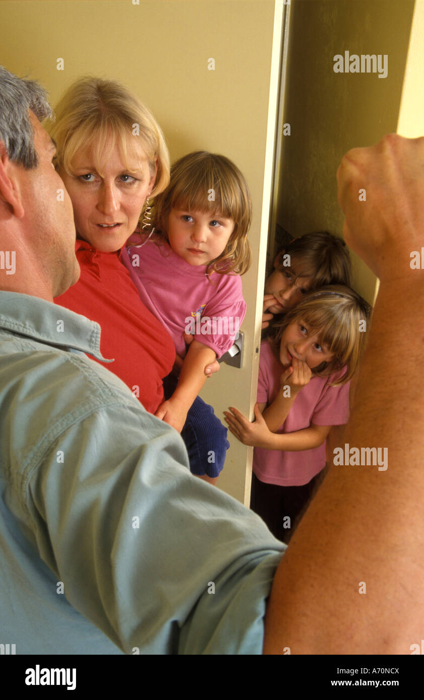 man about to hit a woman who is holding a child - Stock Image