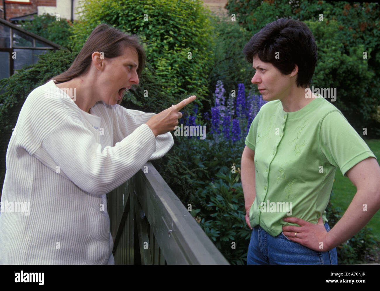 two women fighting over the fence - Stock Image