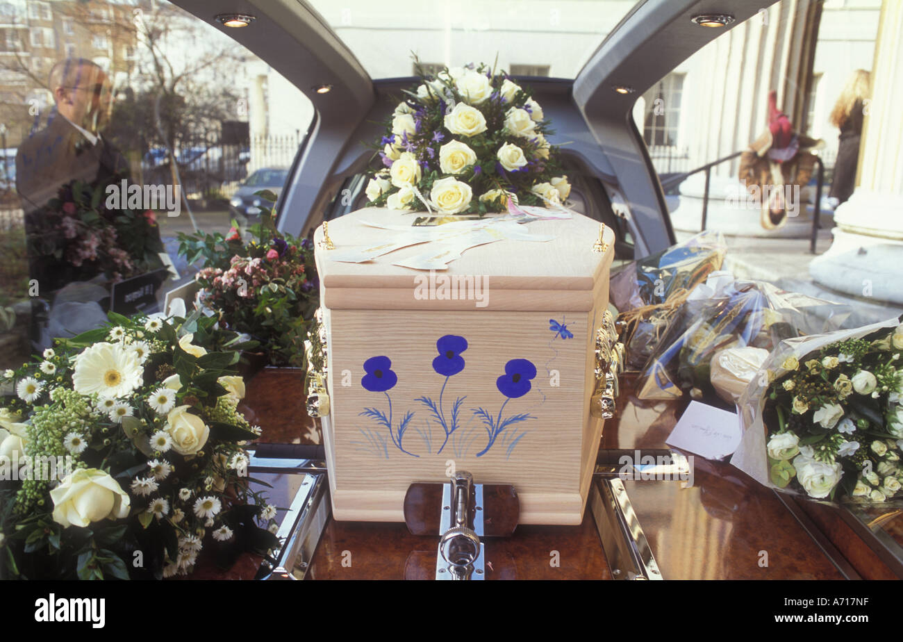 A coffin inside a hearse painted with blue flowers - Stock Image