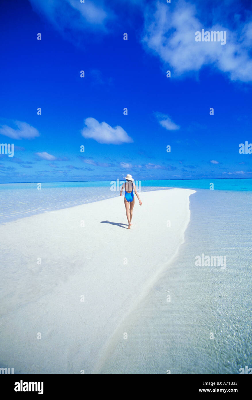 Woman in swimsuit walking on sandbar in Aitutaki Lagoon in the Cook Islands South Pacific Ocean model released image - Stock Image