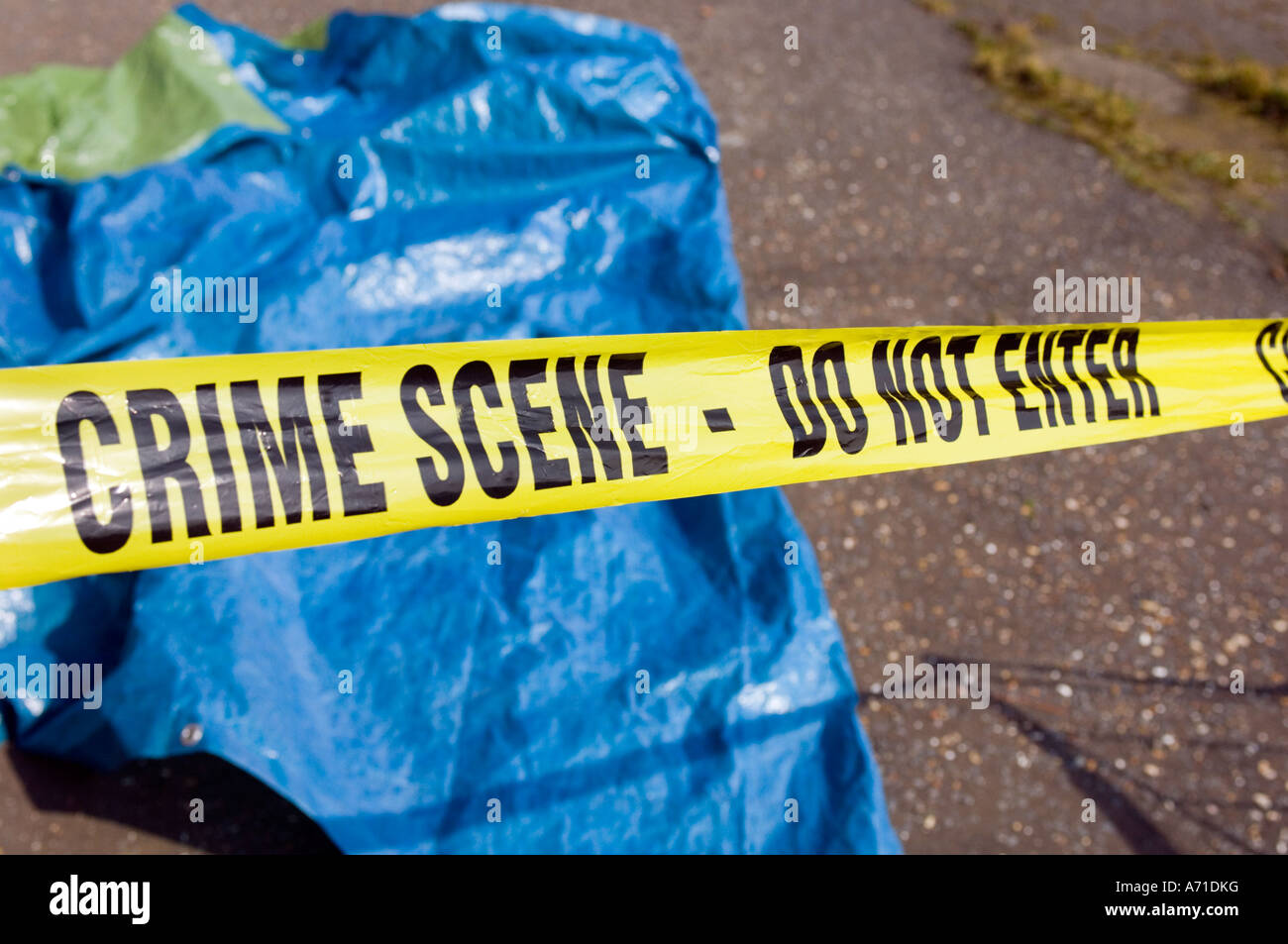 yellow police tape cordoning off a crime scene - Stock Image