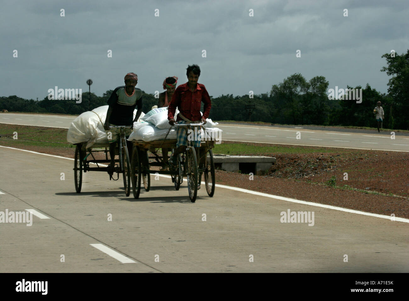 Three rickshaw puller speeding on the highway in the remote India - Stock Image