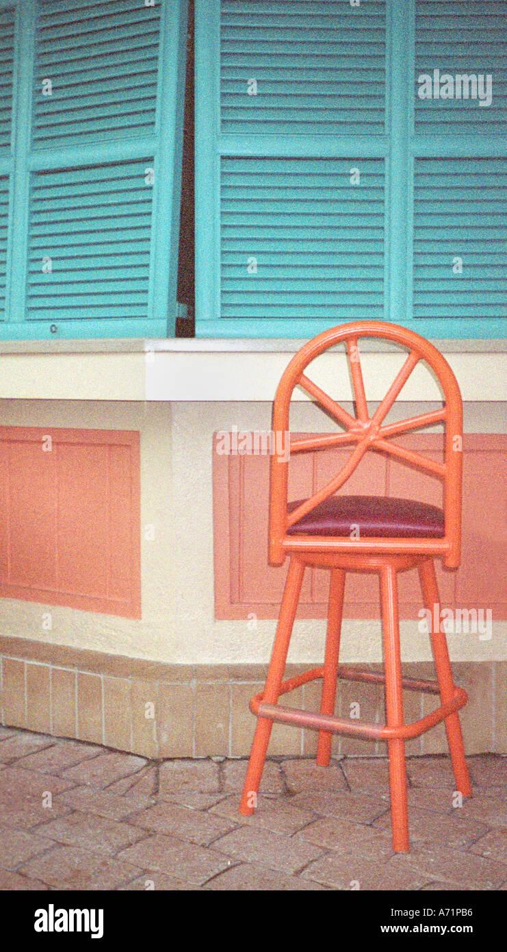 Grainy Orange Chair and Green Shutters Restaurant St Martin Caribbean - Stock Image