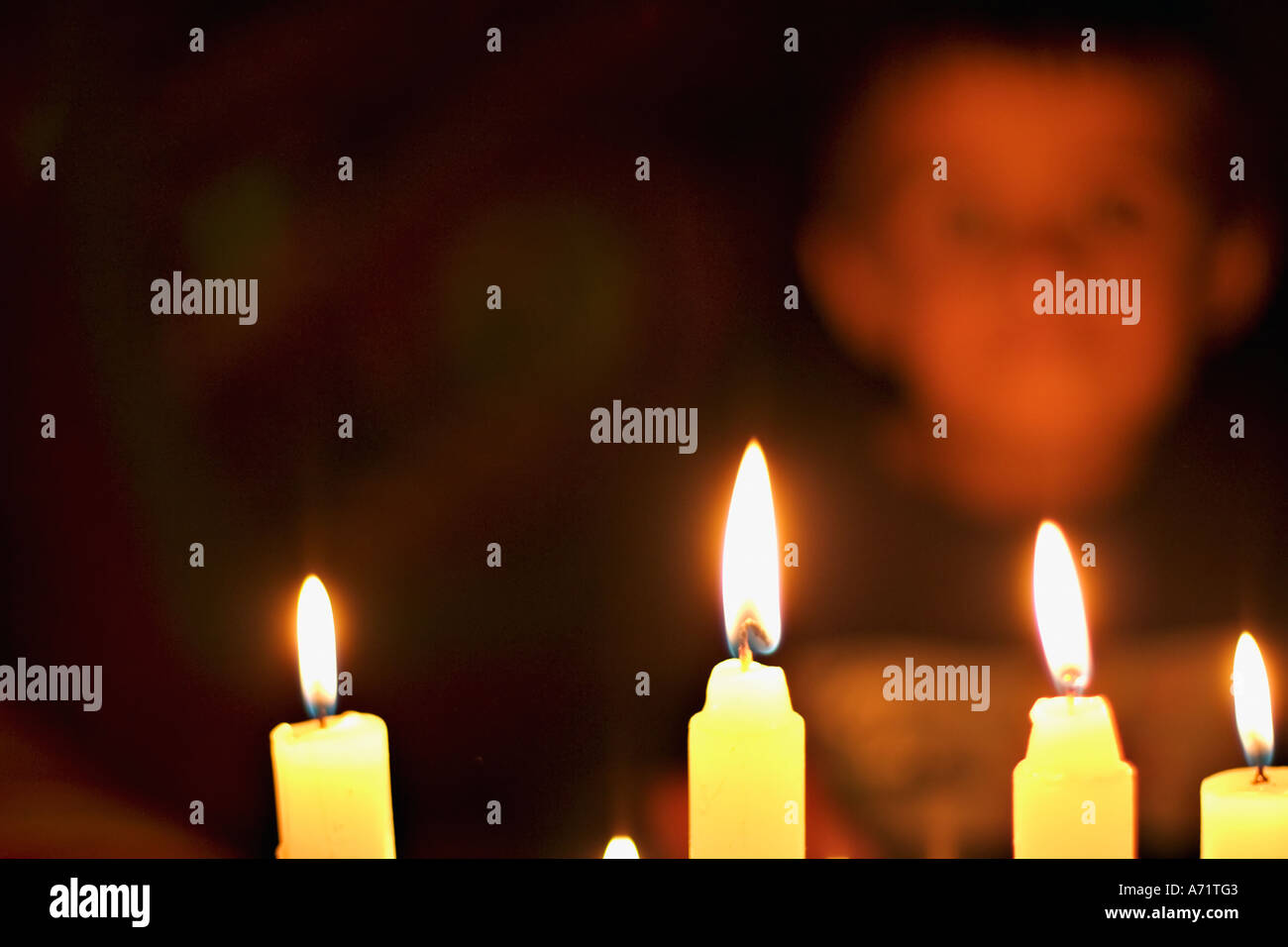 Head and shoulders colour portrait of small children in candlelight - Stock Image