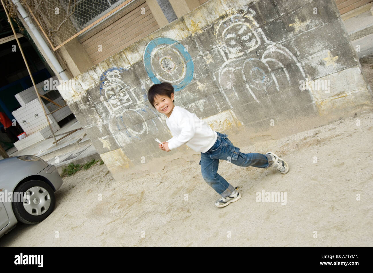 Boy playing in schoolyard - Stock Image