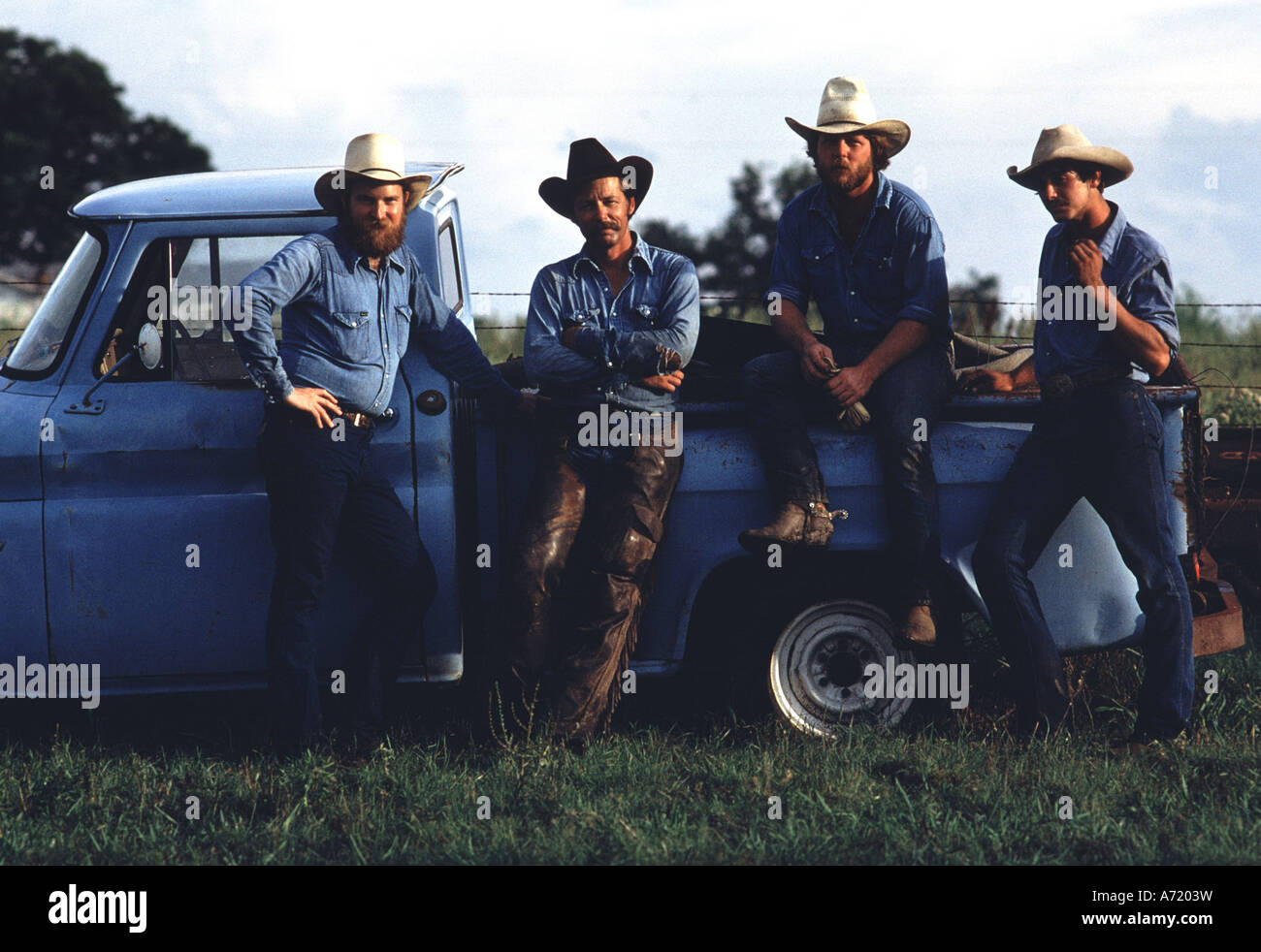After work, four tough cowboys sit by an old blue pick up truck - Stock Image
