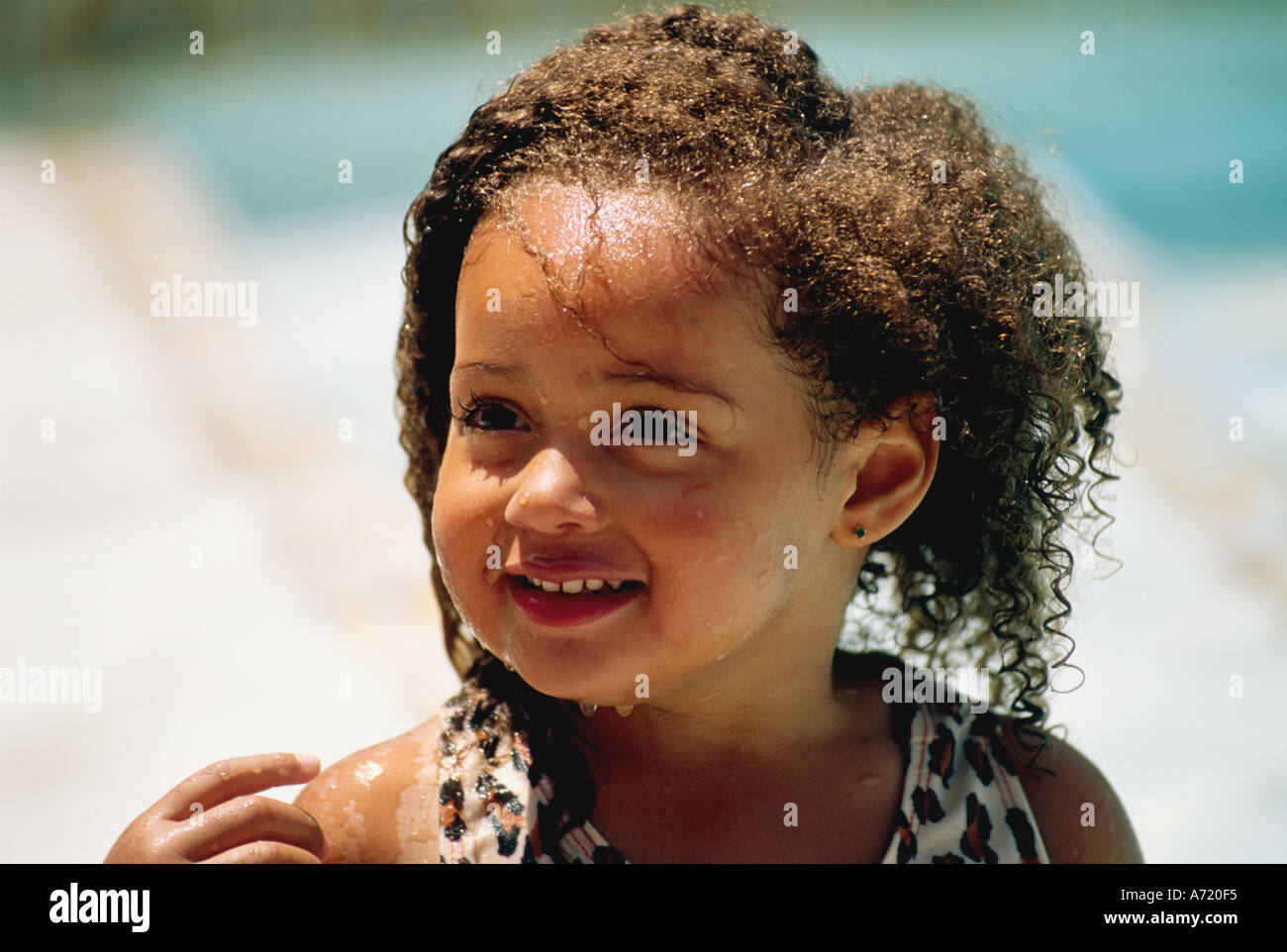 Close up of a young African American girl who has just come out of the pool - Stock Image