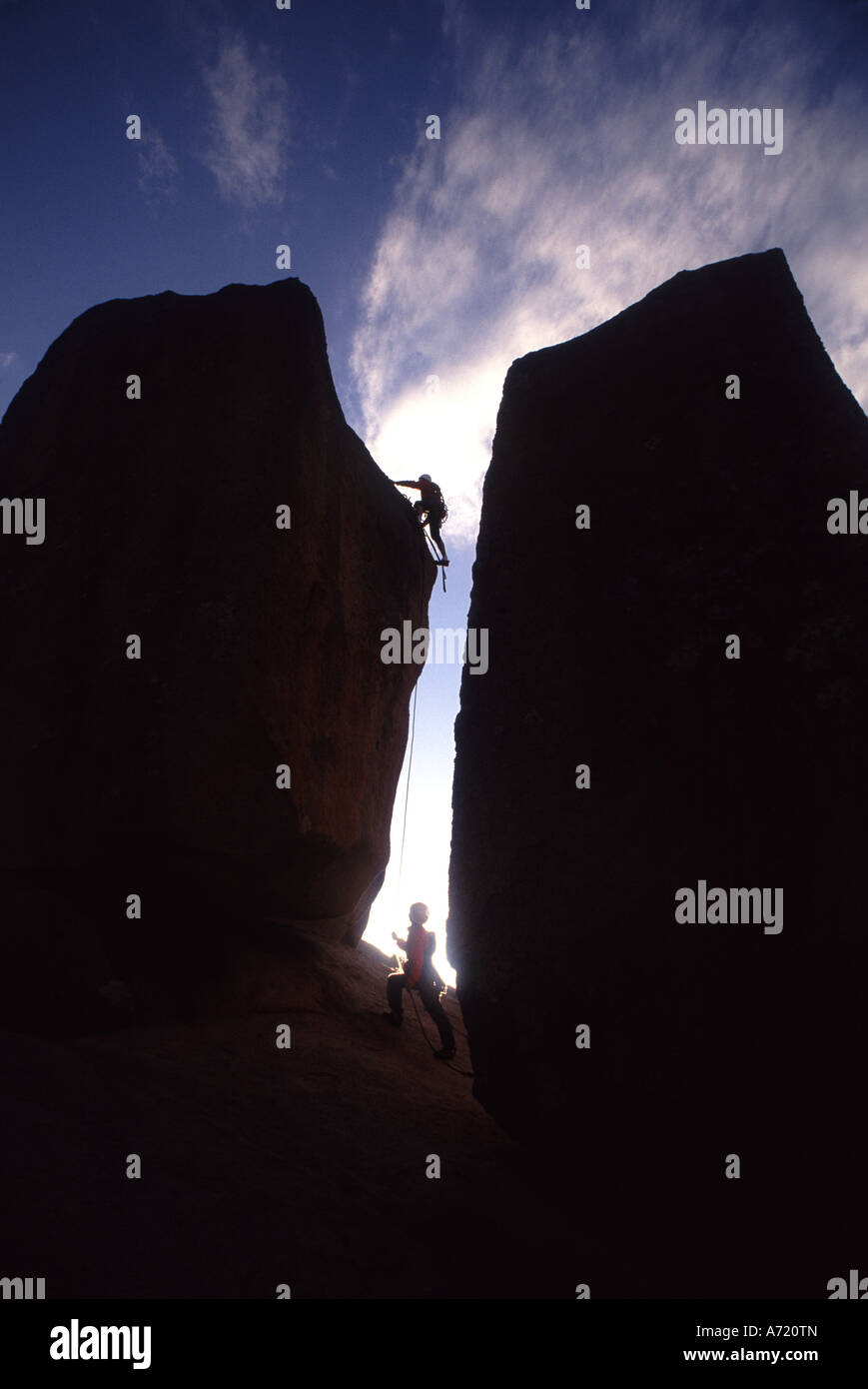 The silhouette of two men can be seen rock climbing - Stock Image