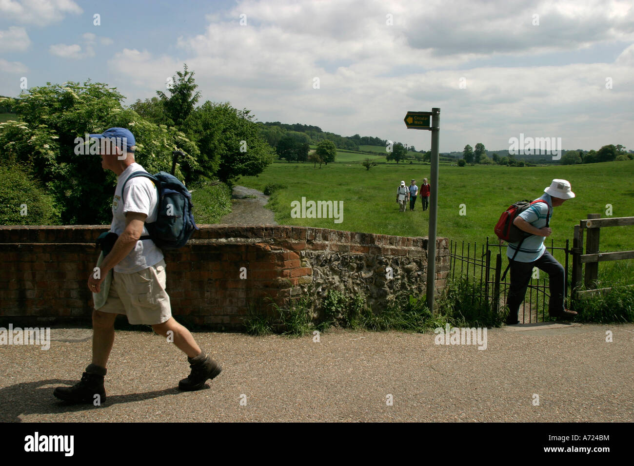 Ramblers on the Chiltern Way walk though through fields into the village of Hambleden - Stock Image