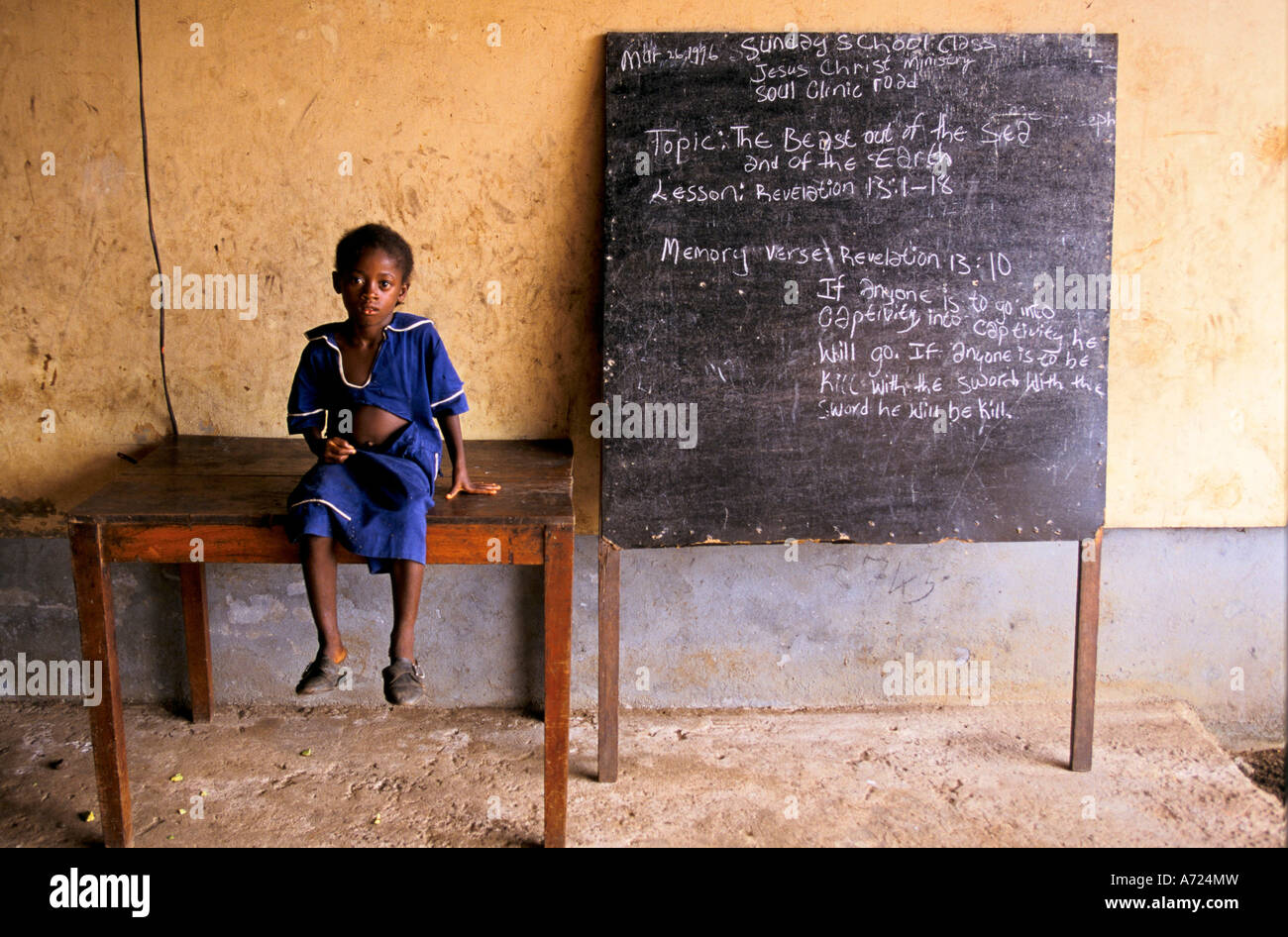 A small girl sits on a wooden table at St Peter s Orphanage - Stock Image