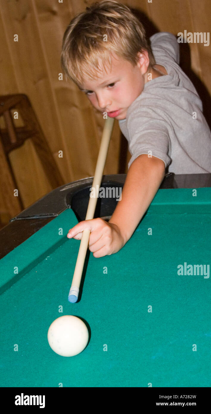 Boy age 7 with pool cue ready to take his shot.  Ashby Minnesota USA - Stock Image