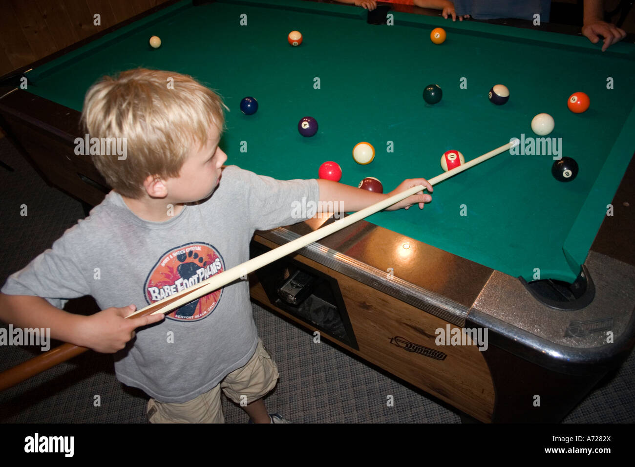 Boy age 7 with pool cue lining up his next shot.  Ashby Minnesota USA - Stock Image