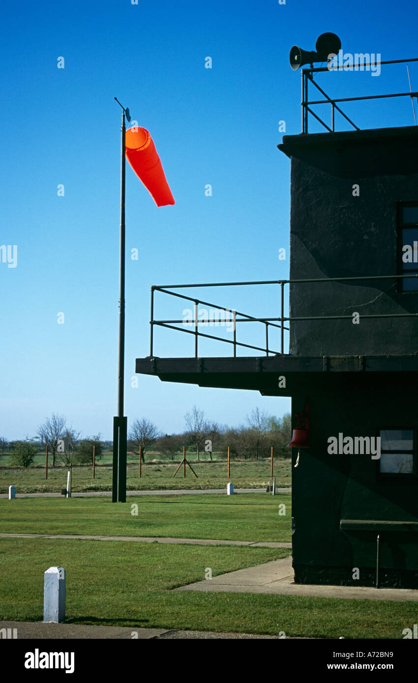 Red/orange windsock blowing in medium breeze with corner of operations centre in foreground - Stock Image