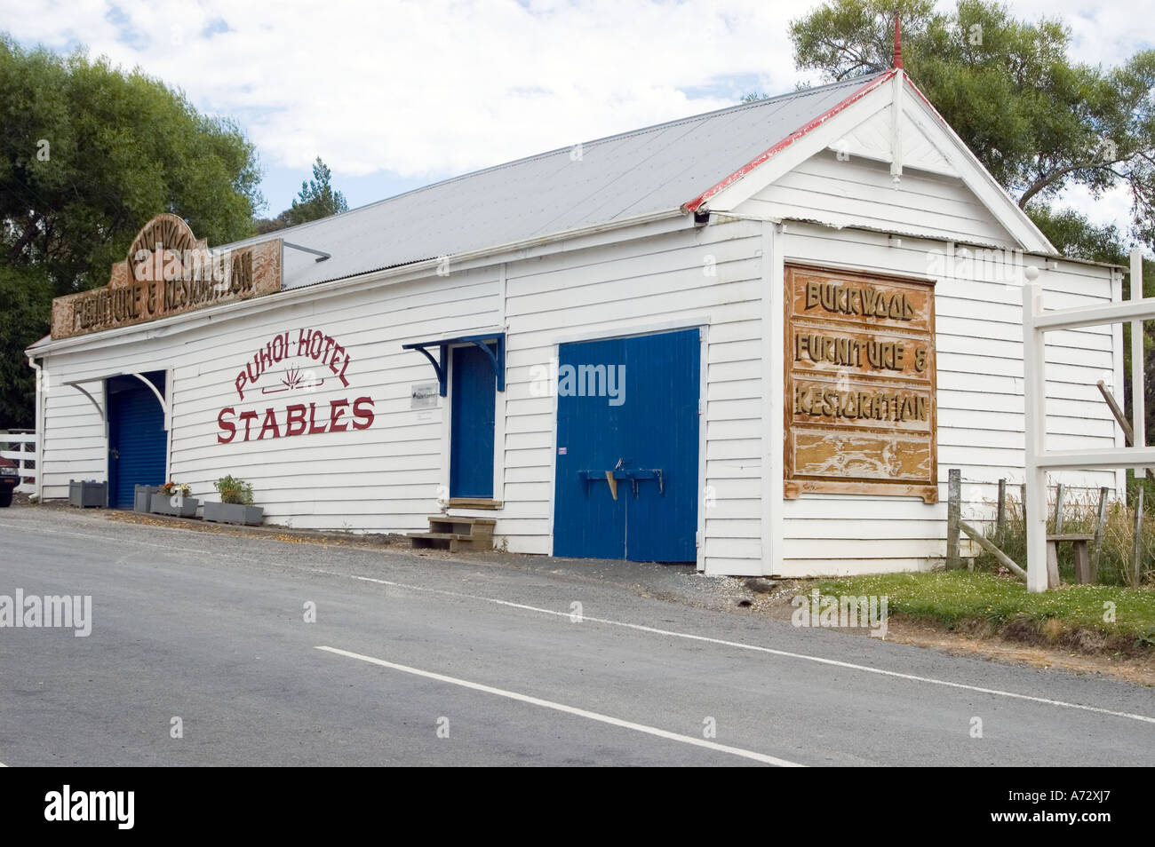 Building with sign showing stables at Puhoi
