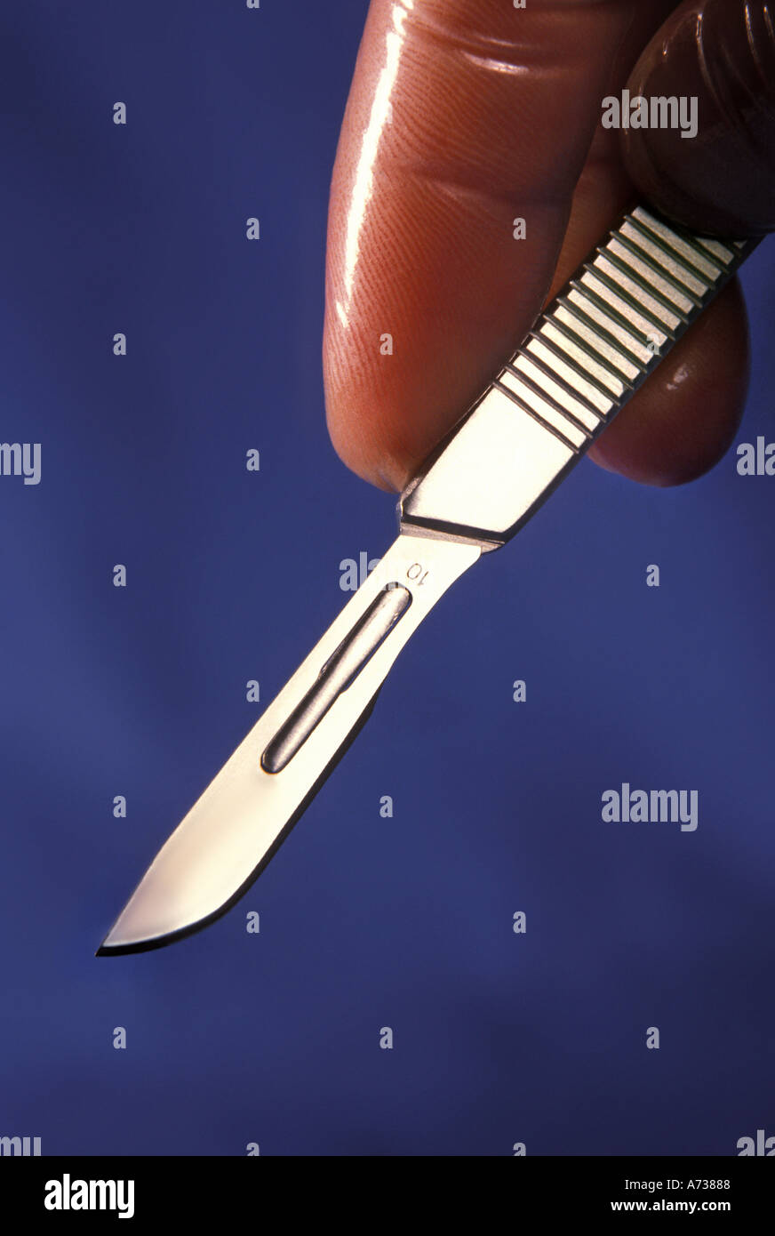 latex gloved hand holding surgical scalpel Stock Photo