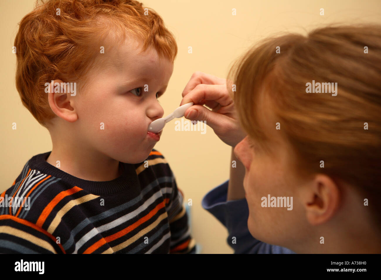 Boy taking medicine from a spoon held by his mother - Stock Image