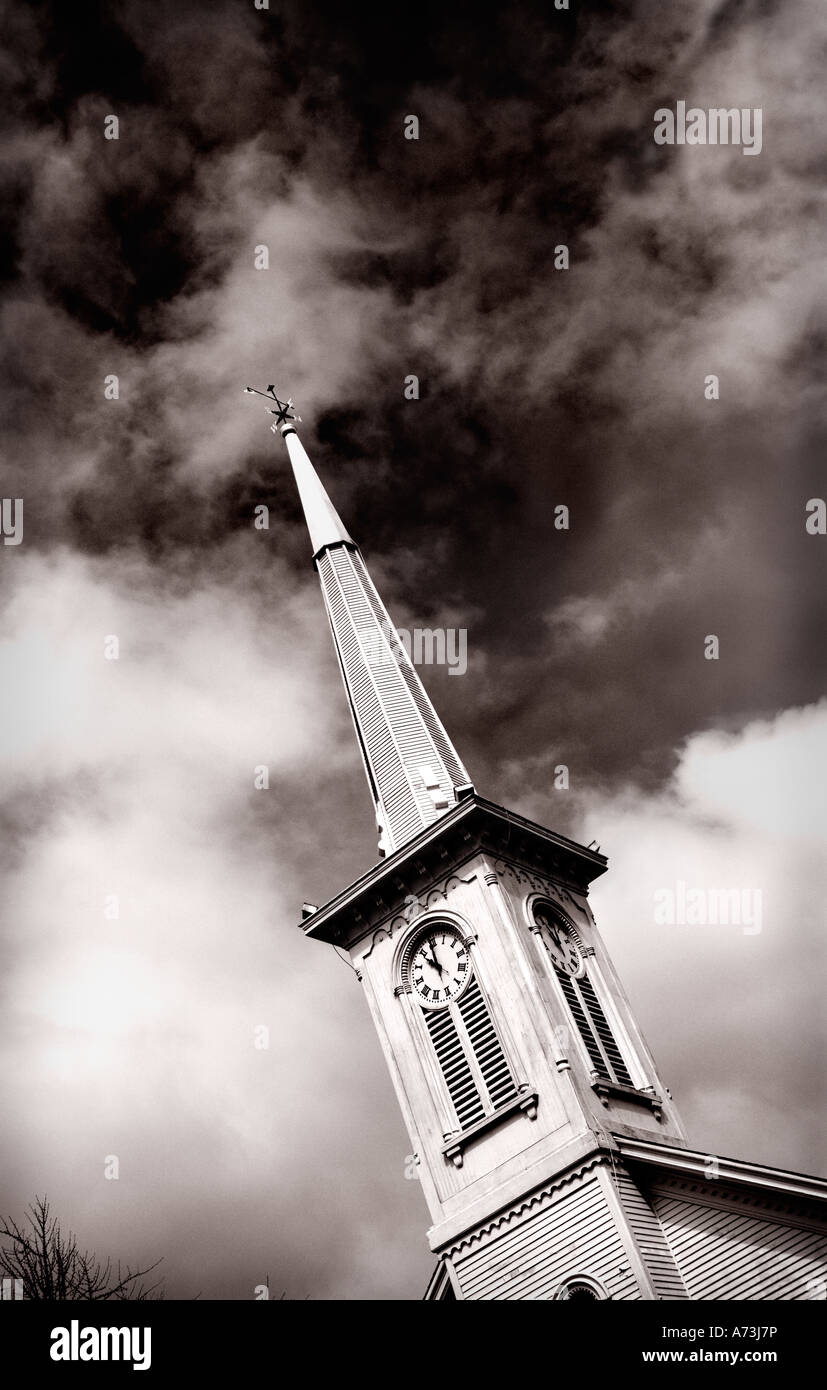 old clock tower with weather vane on top of the steeple in sepia tones looking upwards against a dark stormy sky - Stock Image