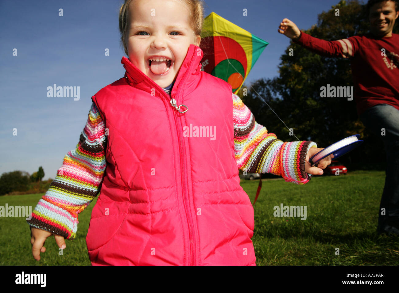 father and daughter playing with kite - Stock Image