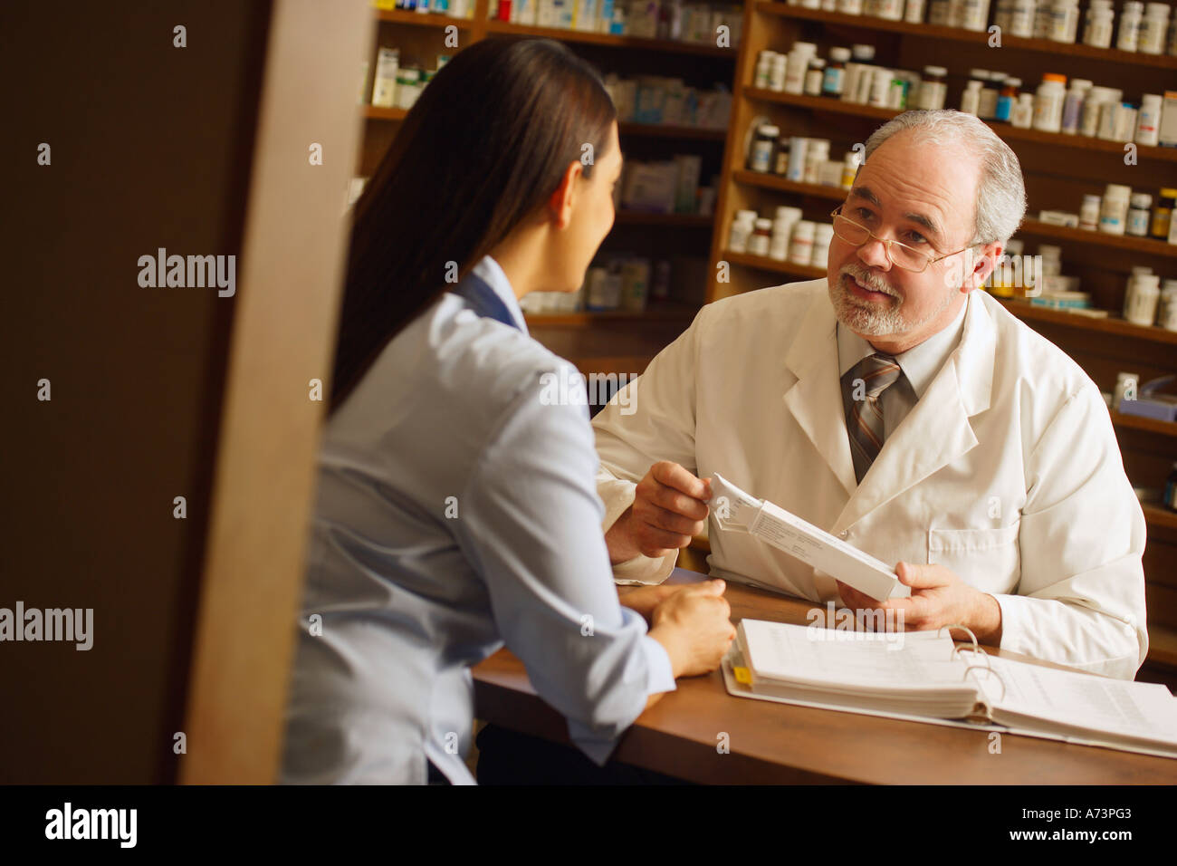 A young woman seeking advise from an older man at a pharmacy - Stock Image