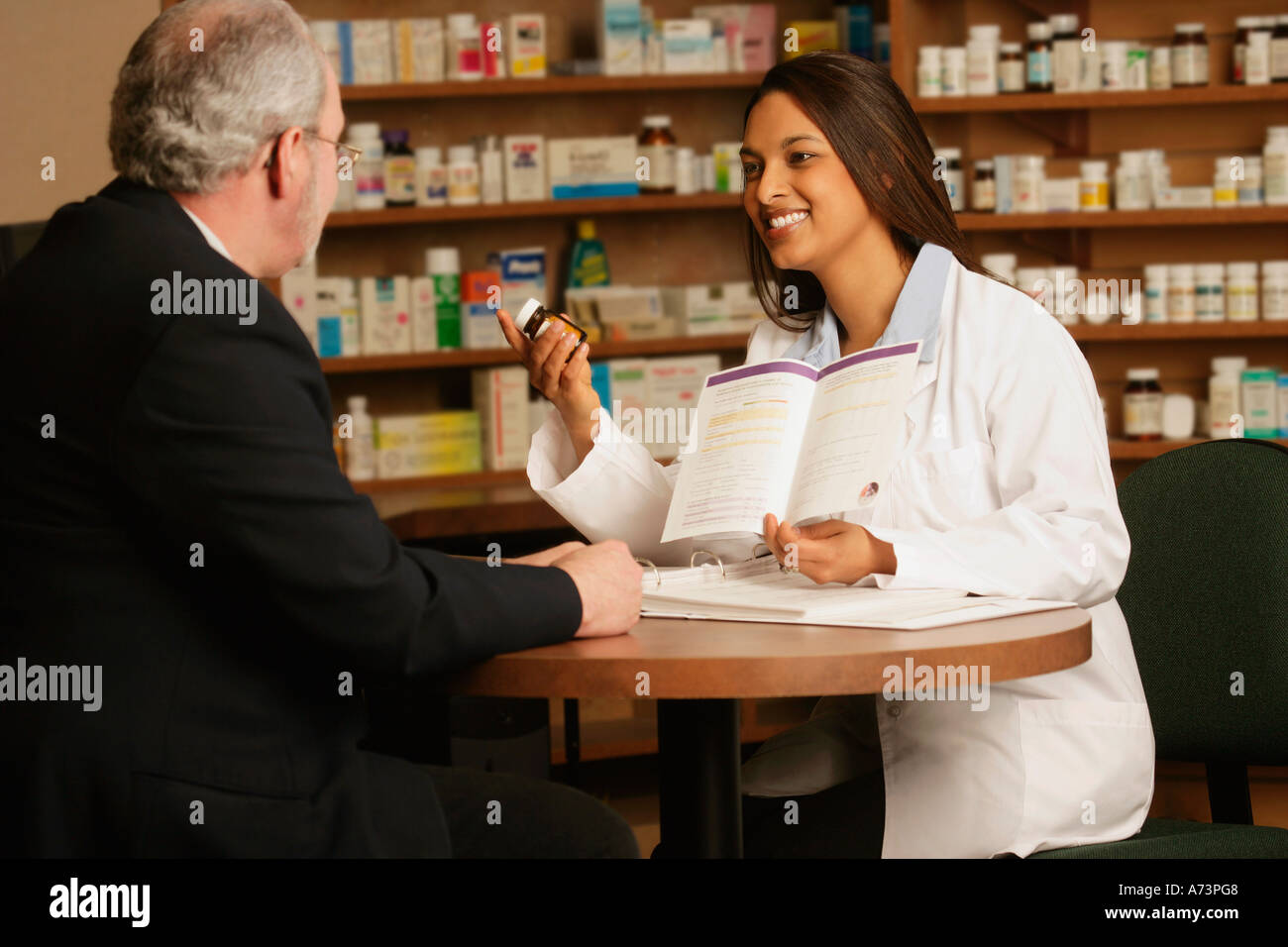 An older man seeking advice from a oung lady working at a pharmacy - Stock Image
