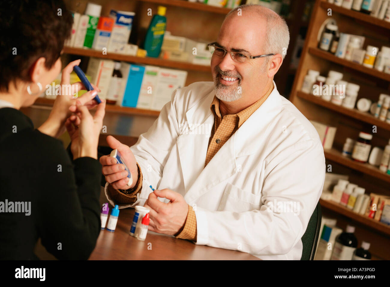 A customer seeks advise from a pharmacist - Stock Image