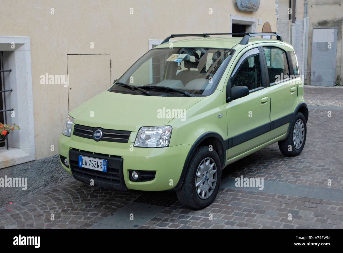 a-green-fiat-panda-car-parked-at-the-side-of-the-street-in-italy