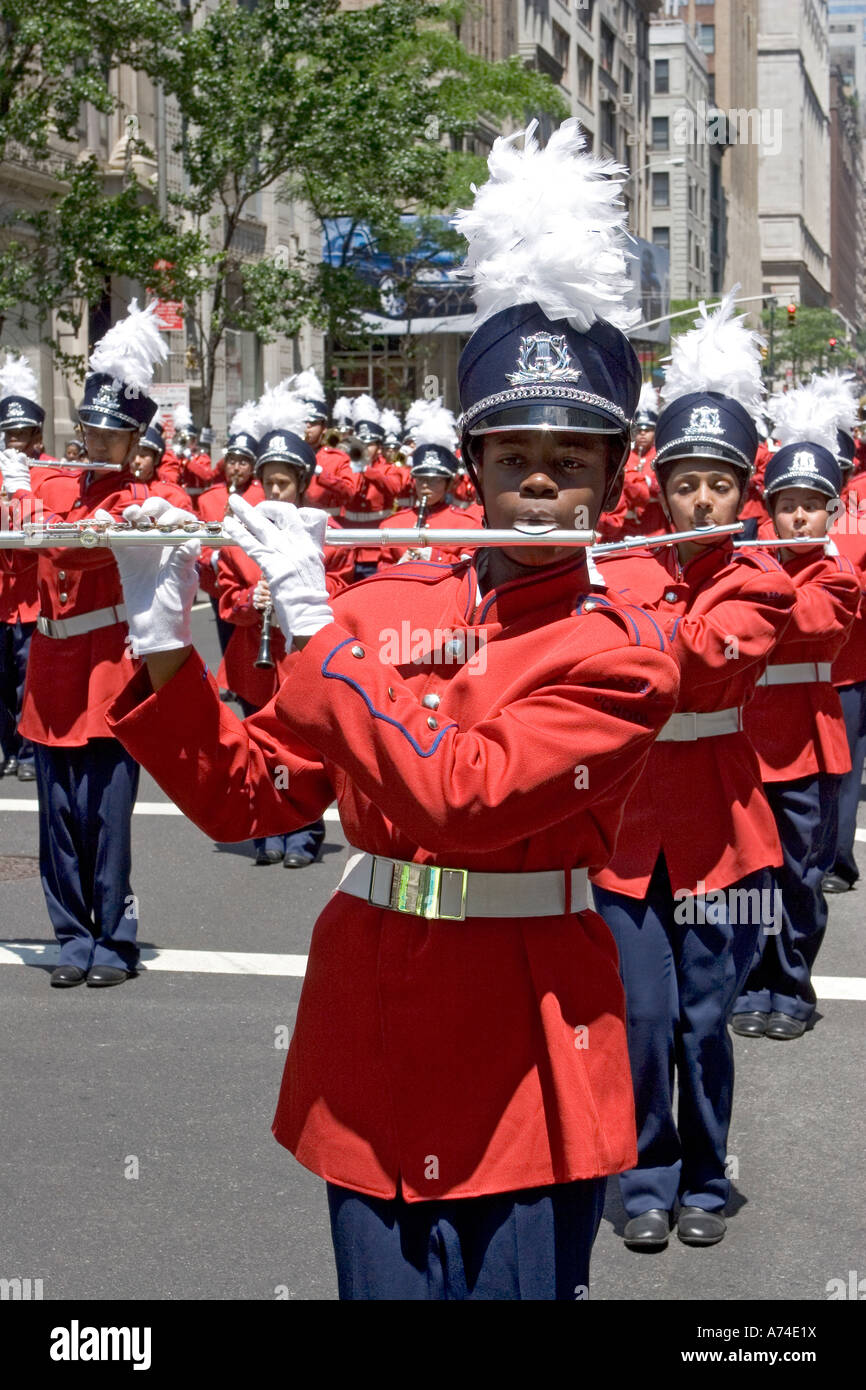 member of a high school band plays the flute as he marches down Madison Avenue in New York City - Stock Image