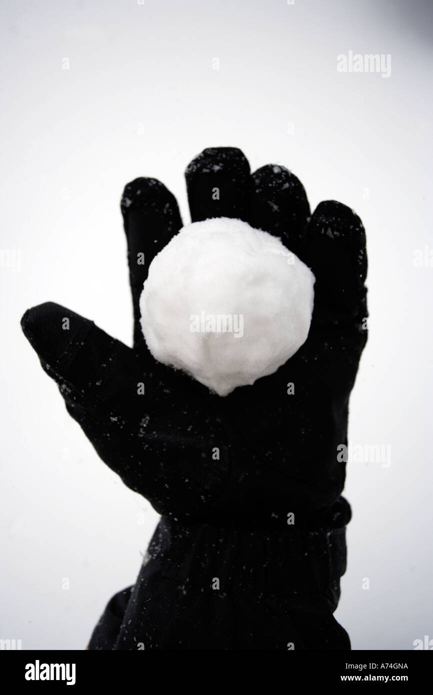 Gloved hand holding snowball, snowball in hand - Stock Image