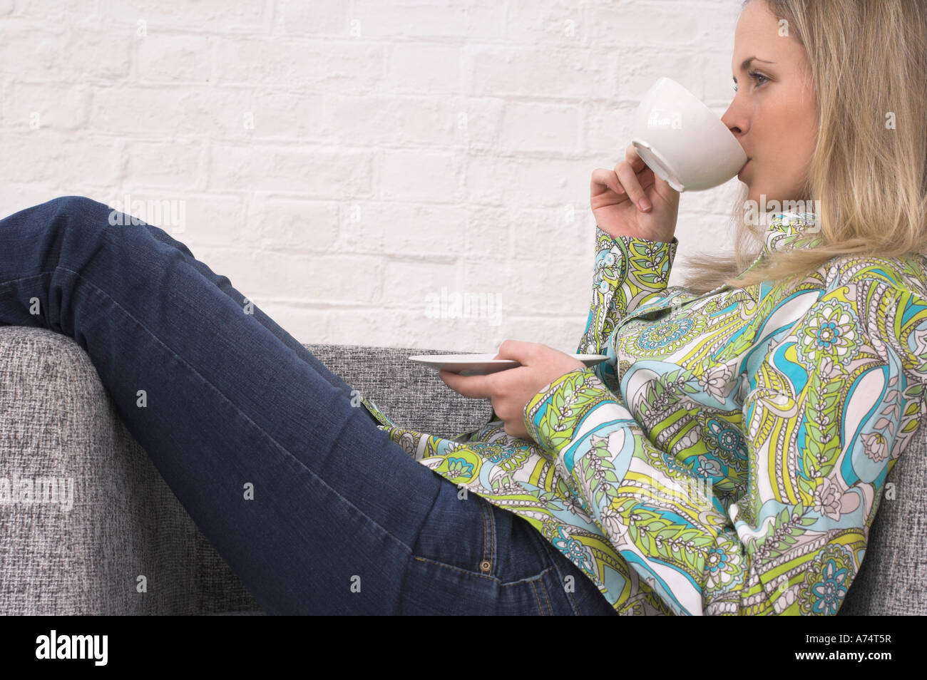 side view of young woman relaxing on armchair drinking cup of tea Stock Photo