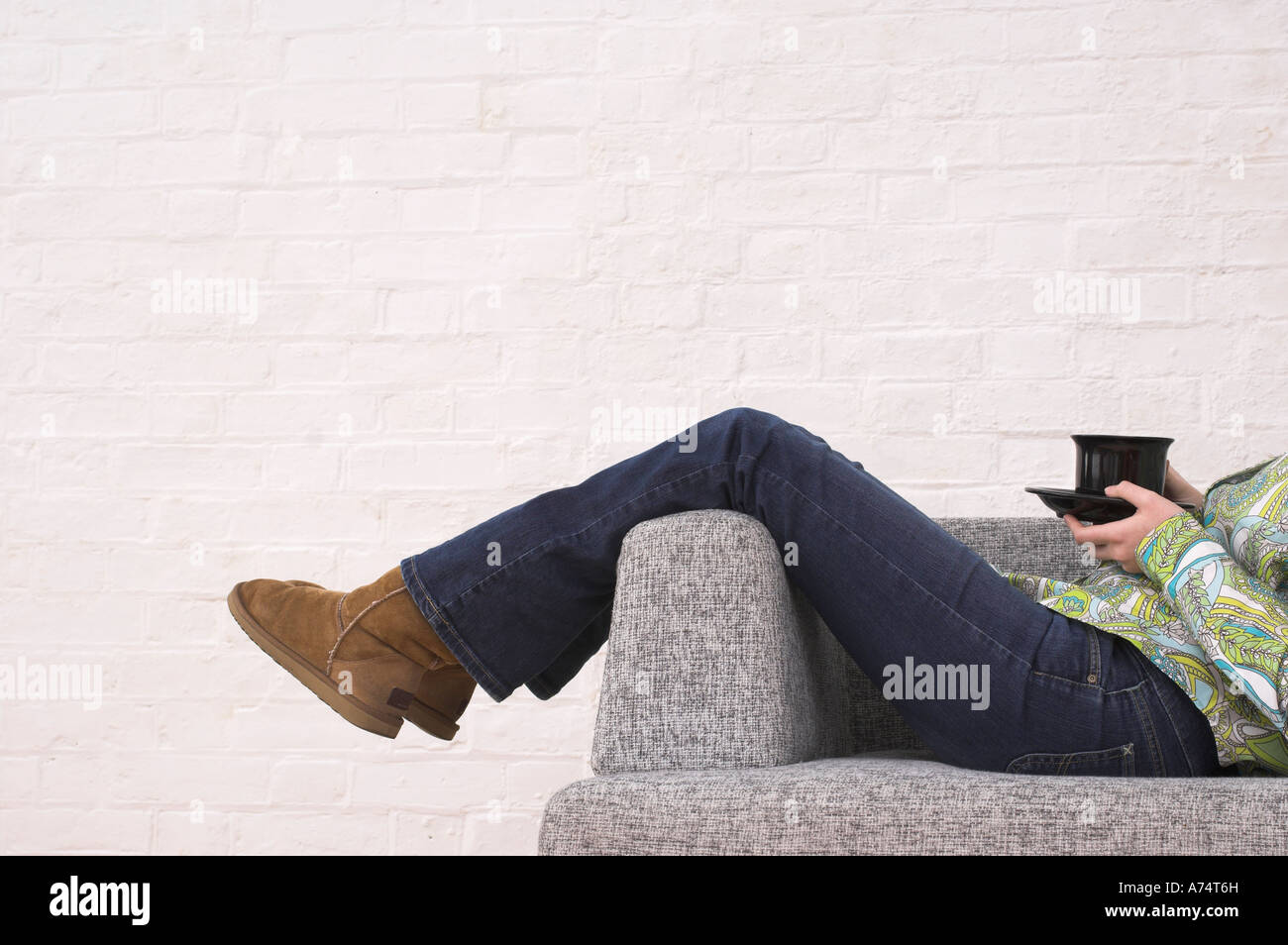 legs of woman taking a rest on armchair holding cup of tea Stock Photo