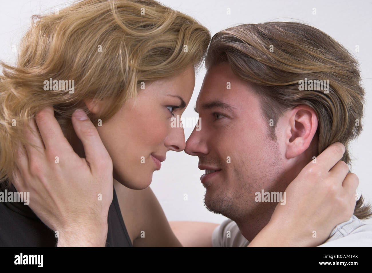 headshot of young couple tenderly looking at each other - Stock Image