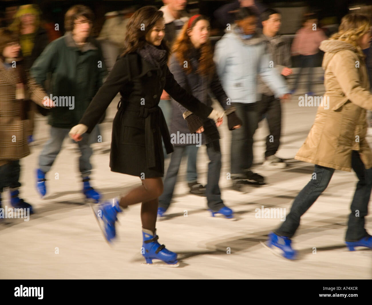ice skaters speeding past in blurred motion - Stock Image