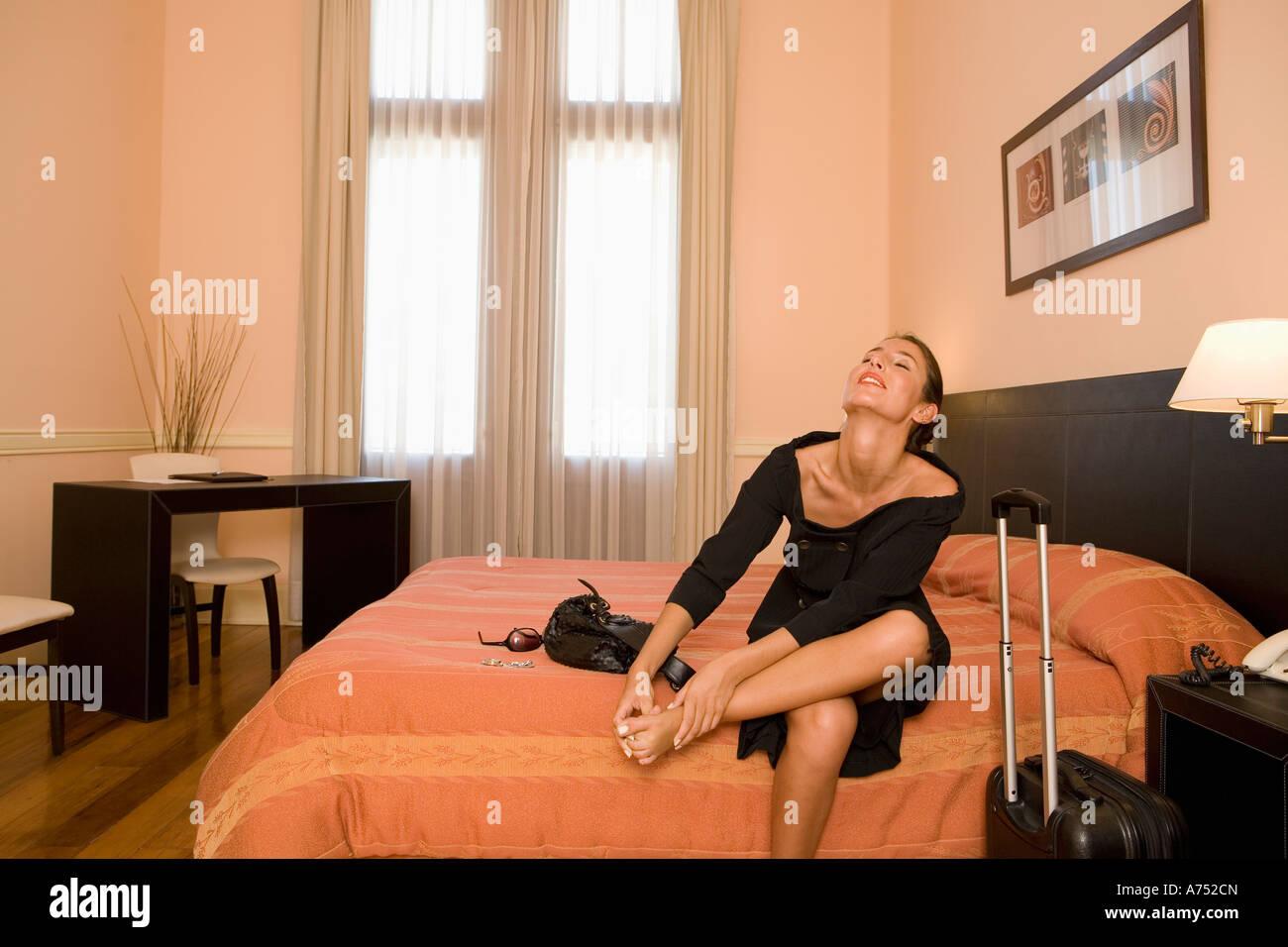 Businesswoman rubbing her feet in hotel room Stock Photo