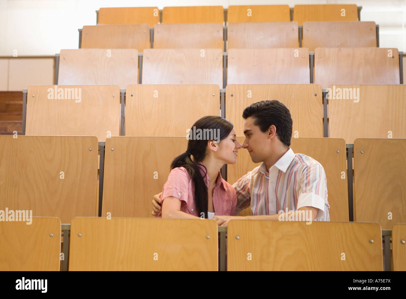 Students kissing in empty classroom Stock Photo