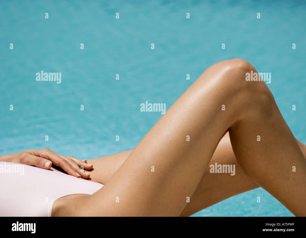 Woman lying by side of pool, partial view - Stock Image