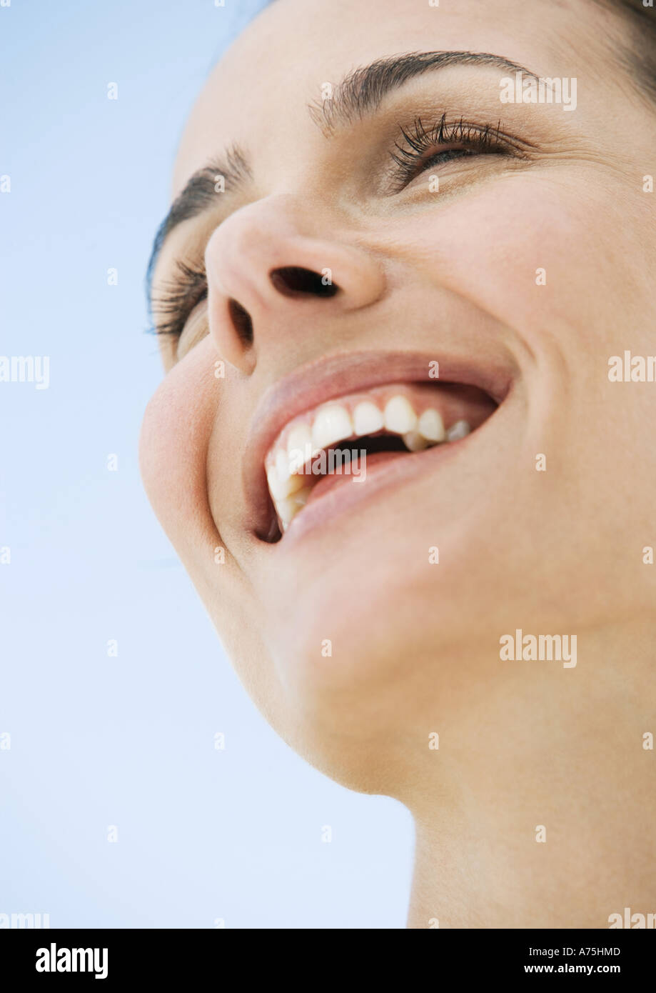 Woman smiling, low angle view - Stock Image