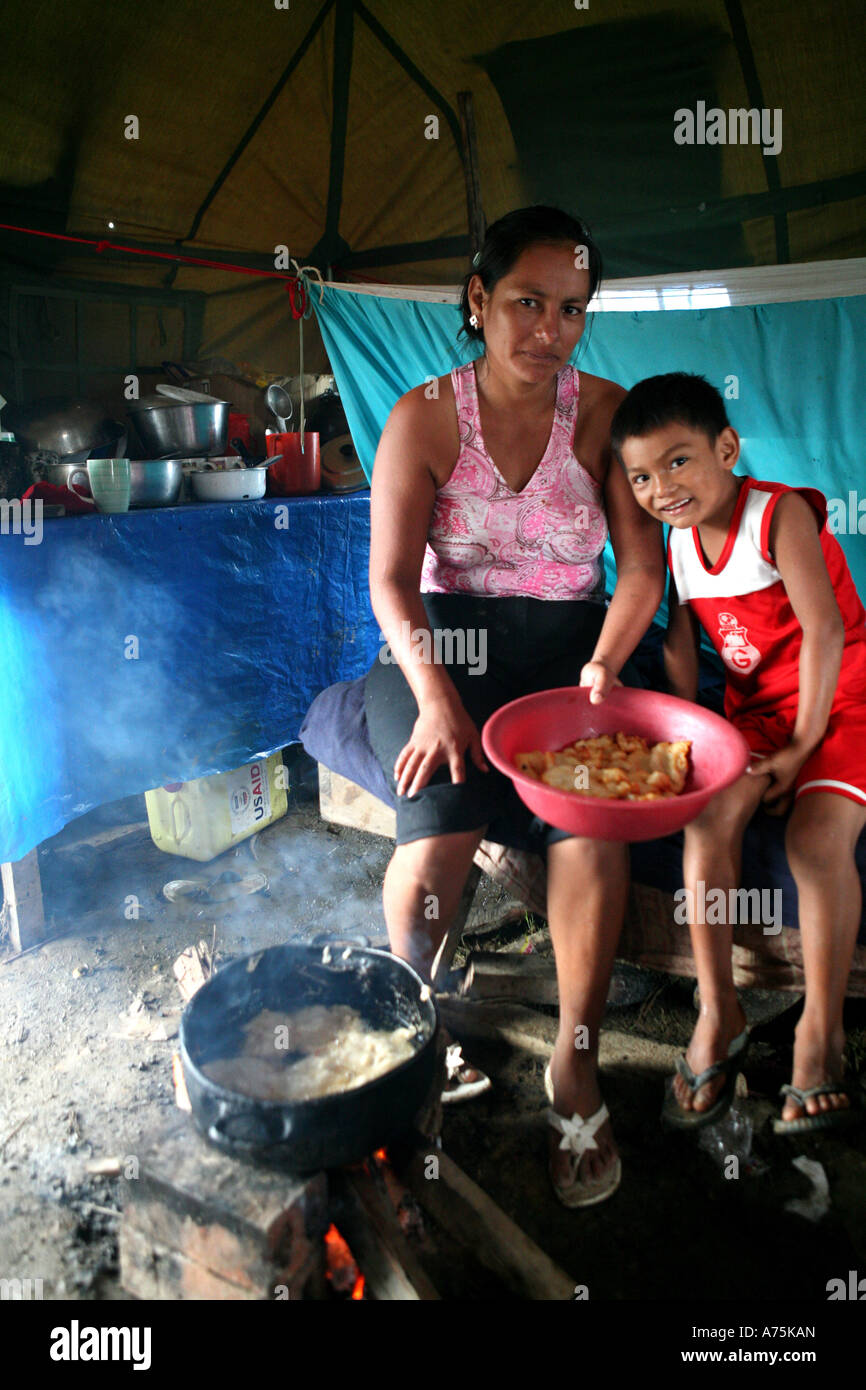 Family cooking inside a shelter on the outskirts of Trinidad, badly effected by flooding, Beni, Bolivia, South America Stock Photo