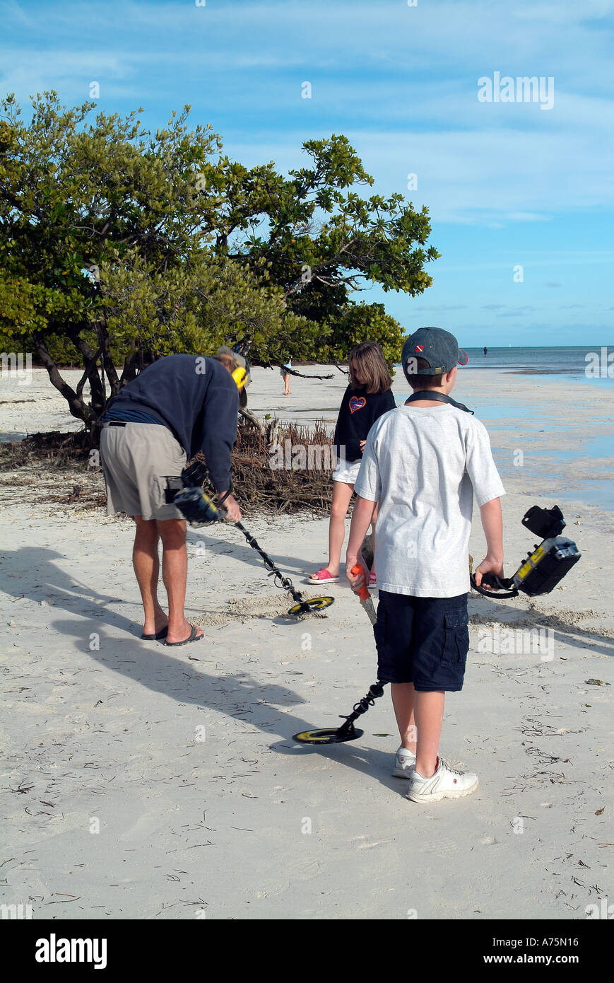 Treasure hunters with their metal detector on a beach - Stock Image