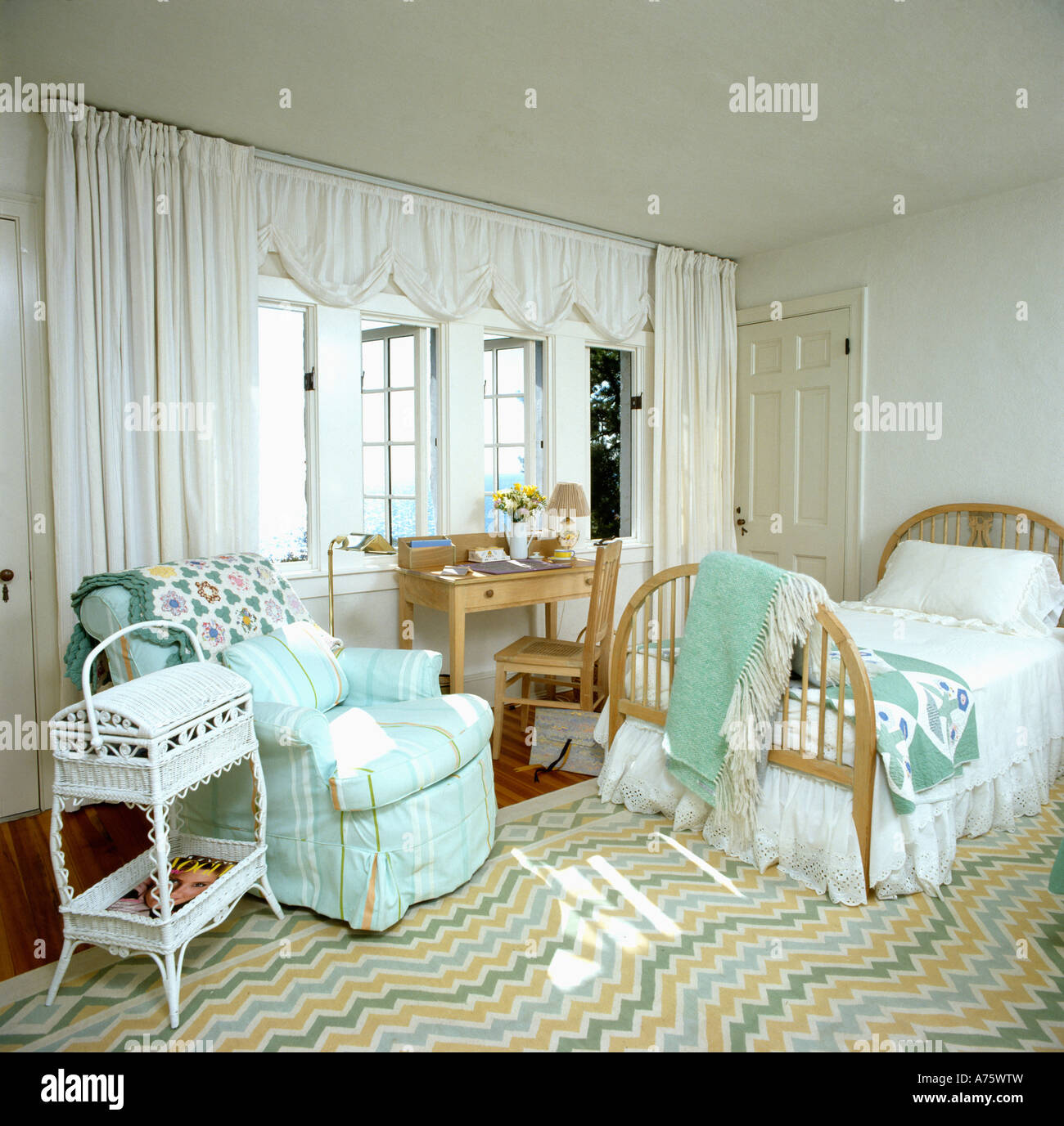 Seaside bedroom with turquoise loosecover on armchair and ...